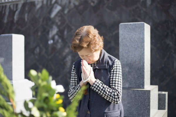 墓に向かって手を合わせる女性