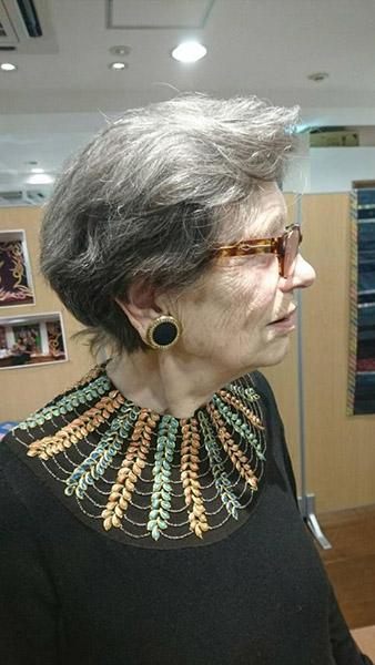 市販の黒いシンプルなニットの襟元に、気に入ったアンティークの刺繍を縫い付けています。