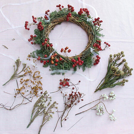 ナンキンハゼの実(右下の白い実)や野バラの実(中央)などいろんな実を、籐の隙間に挿しこんでいく