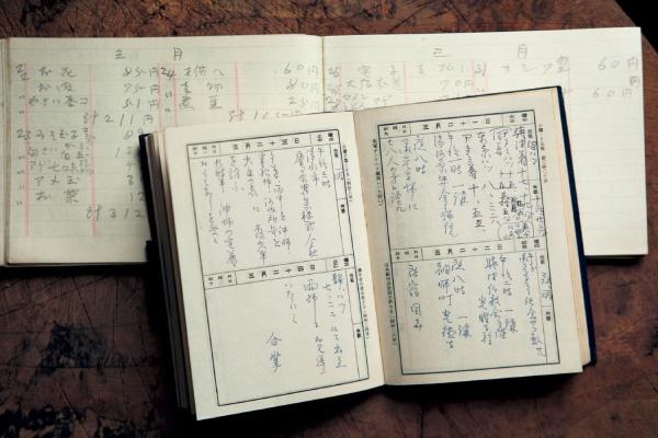 万年筆の細かい字で書かれた家計簿(奥)と講演の記録(手前)。障害のために小学校へ通わせてもらえなかった久子さんは、文字の読み書きをすべて独学で覚えました