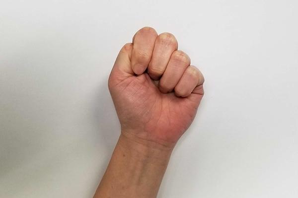 手の指を伸ばすストレッチ方法:親指を中に入れてグッと力強く手を握ります