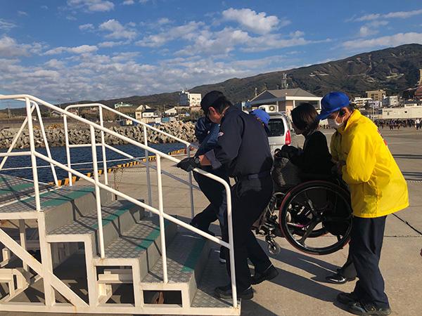 伊豆大島にて、フェリーに乗るために車いすを持ち上げ階段を運んでサポートしていただいている様子