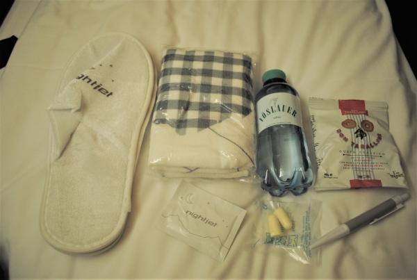 紙袋の中には、スリッパ、「ナイトジェット」のオリジナルタオル、水、おしぼり、スナック、耳栓、ボールペンが入っていました
