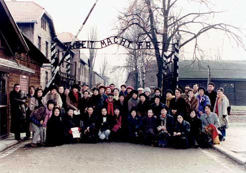 アウシュビッツの門の前で