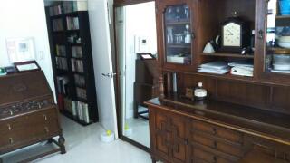 右の姿見の後ろにテーブルの天板。ドアの向こうは廊下の本棚。左のライティングビューローにキッチン小物を収納