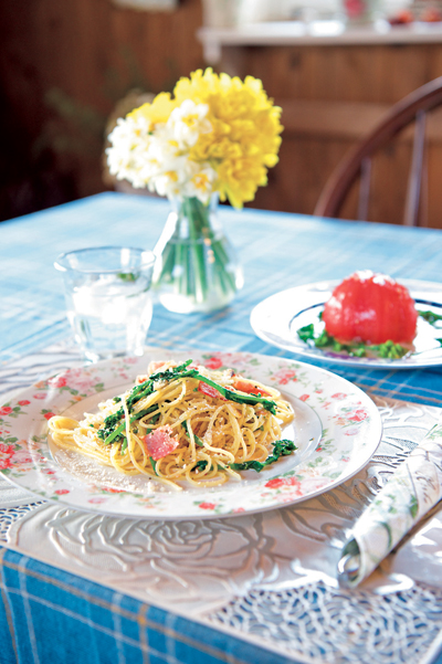 畑でとれたトマトが丸ごと楽しめるお手製のサラダや、菜の花のパスタ。くつろいでほしいと、お皿やキッチンマットなどにもこだわっているそう。