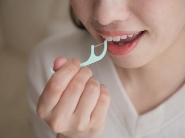 歯間ブラシ(またはフロス)を使っている女性